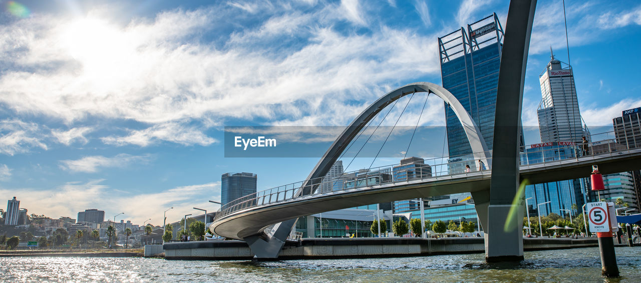 built structure, architecture, building exterior, bridge, water, city, sky, bridge - man made structure, cloud - sky, river, connection, transportation, building, day, nature, office building exterior, waterfront, modern, engineering, cityscape, skyscraper, outdoors, arch bridge, financial district