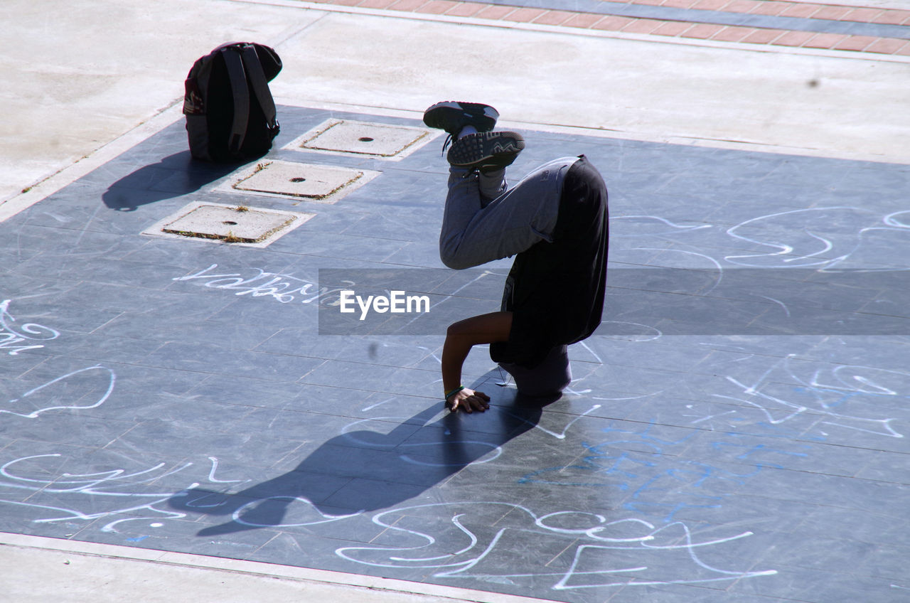 High angle view of mid adult man doing headstand on floor