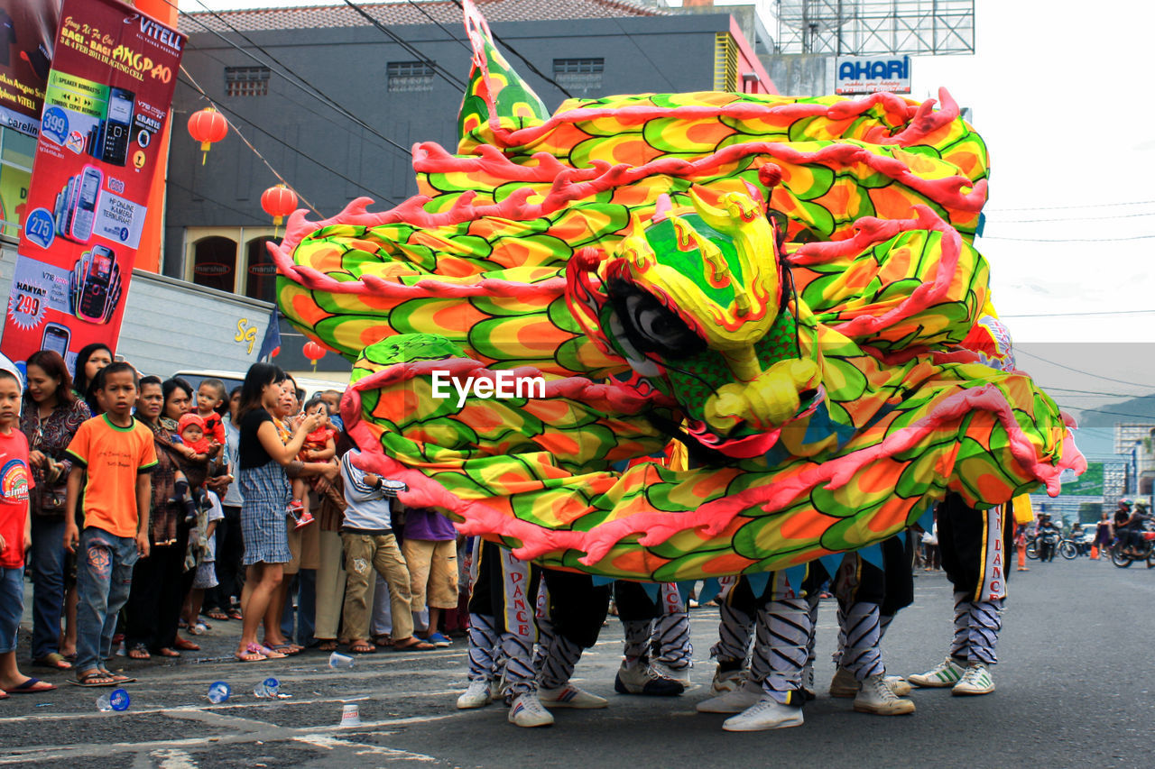 large group of people, real people, celebration, costume, street, leisure activity, dragon, men, mixed age range, traditional festival, women, lifestyles, outdoors, chinese new year, chinese dragon, day, togetherness, teamwork, crowd, city, adult, people