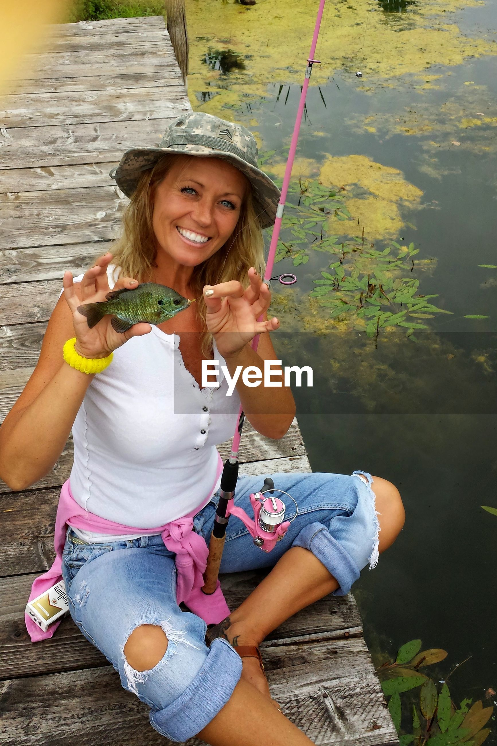 Portrait of smiling mid adult woman showing fish on pier over lake