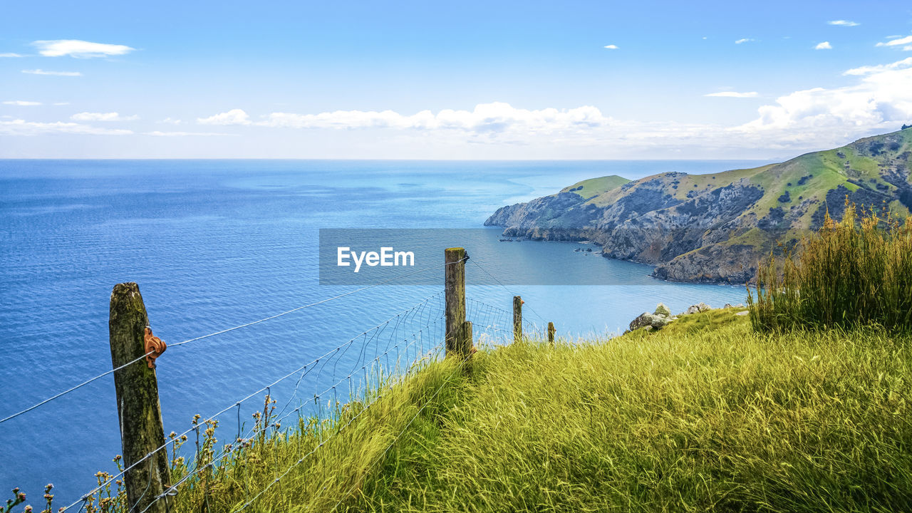 water, sky, sea, scenics - nature, tranquil scene, tranquility, beauty in nature, grass, plant, nature, horizon over water, barrier, land, horizon, fence, no people, boundary, cloud - sky, day, outdoors, wooden post