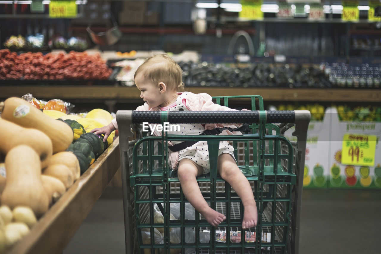 childhood, child, one person, real people, retail, full length, lifestyles, food and drink, casual clothing, shopping cart, store, men, baby, innocence, sitting, leisure activity, food, looking