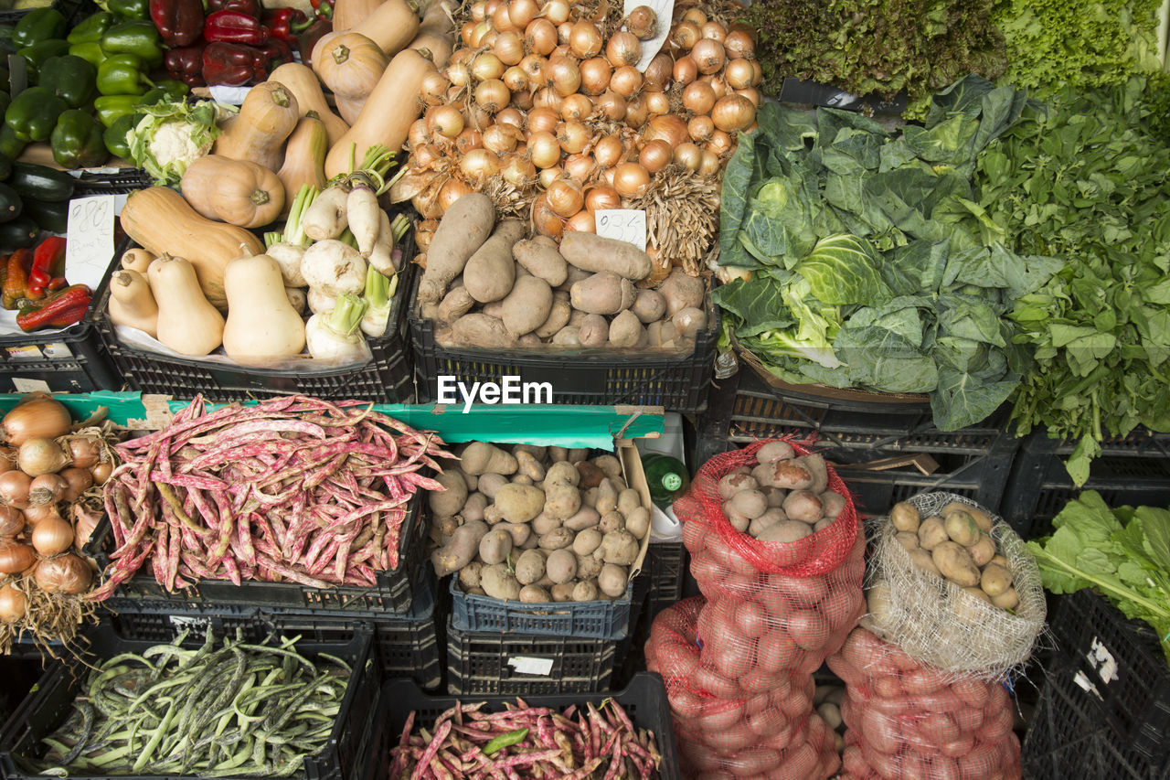 Various vegetables in crates for sale at market stall