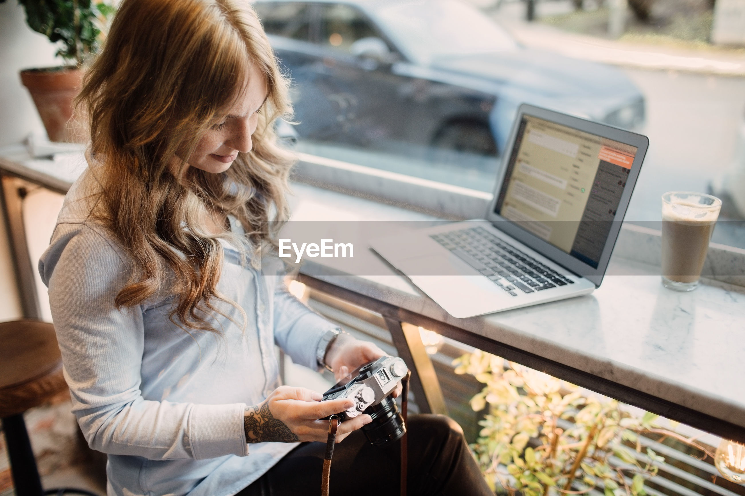 High angle view of young woman holding camera while sitting with laptop at cafe