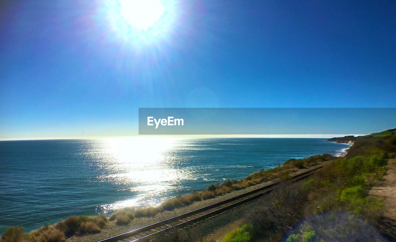 Scenic view of sea against bright blue sky
