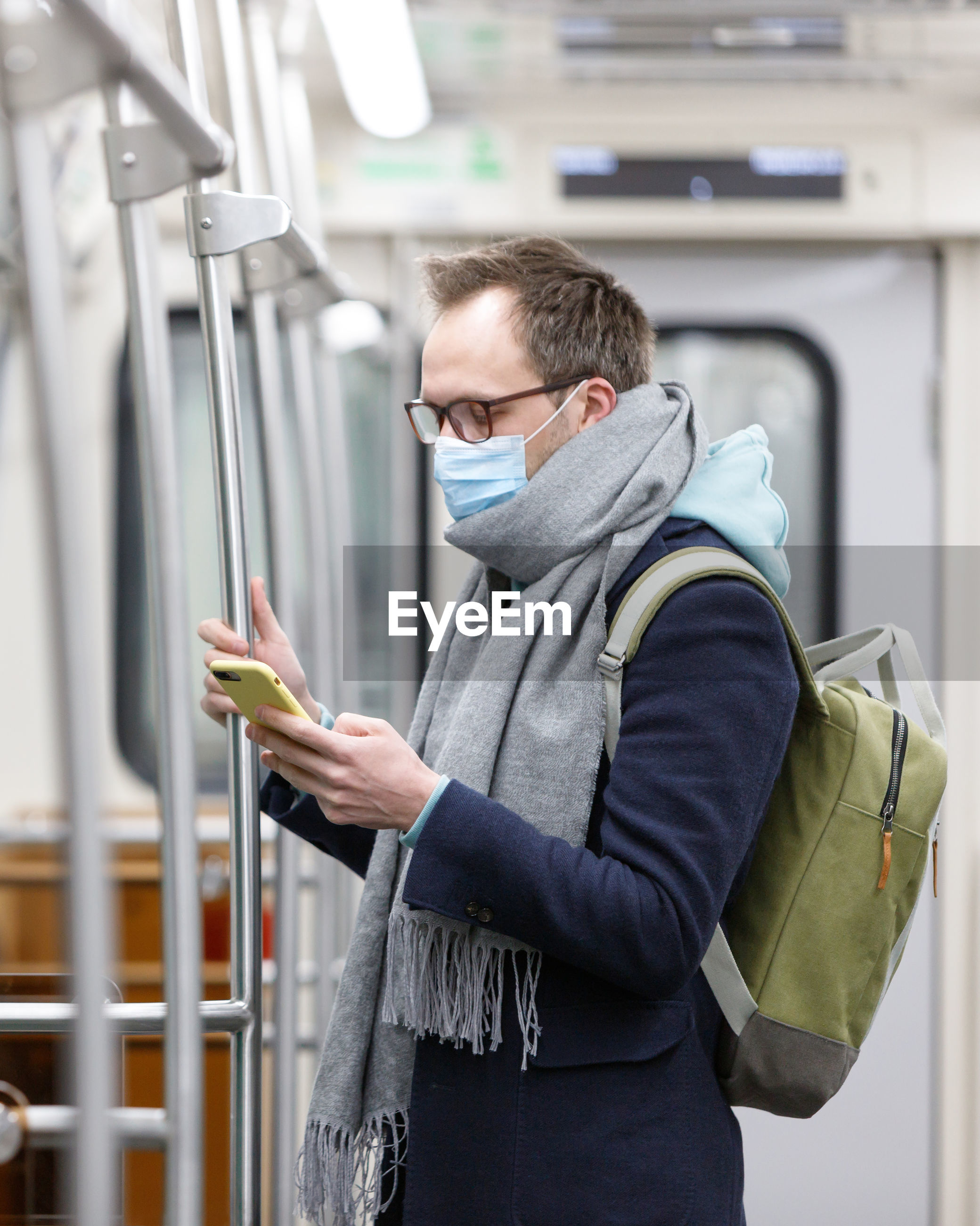 Side view of man wearing mask using smart phone while standing in subway train