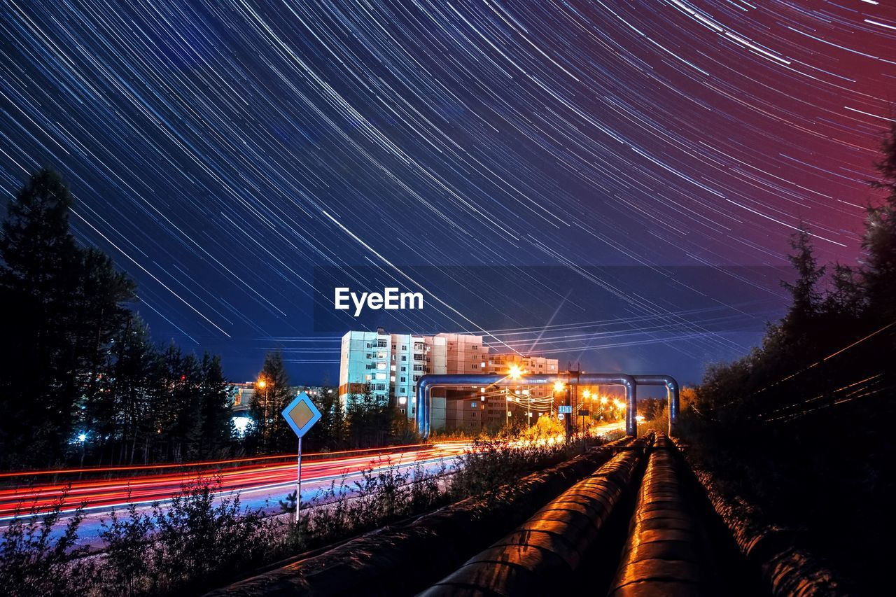 night, astronomy, star - space, illuminated, space, tree, rail transportation, motion, sky, long exposure, no people, plant, transportation, star trail, nature, scenics - nature, architecture, railroad track, track, blurred motion, outdoors