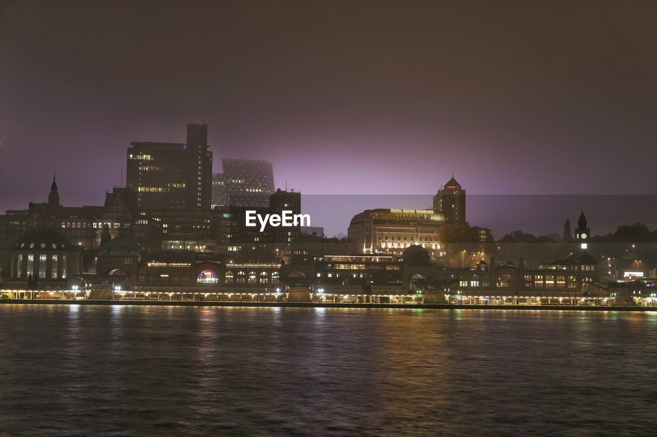 building exterior, architecture, built structure, illuminated, water, sky, city, waterfront, building, river, night, no people, nature, cityscape, travel destinations, office building exterior, outdoors, urban skyline, skyscraper