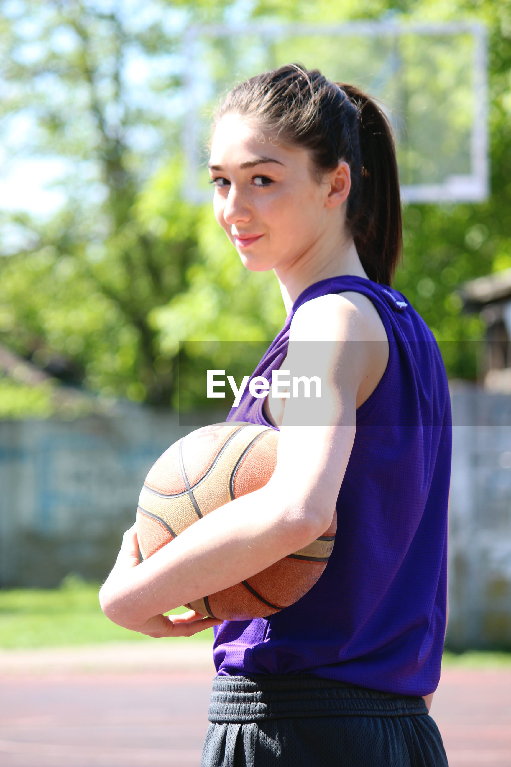 Portrait of smiling woman standing with basketball against trees