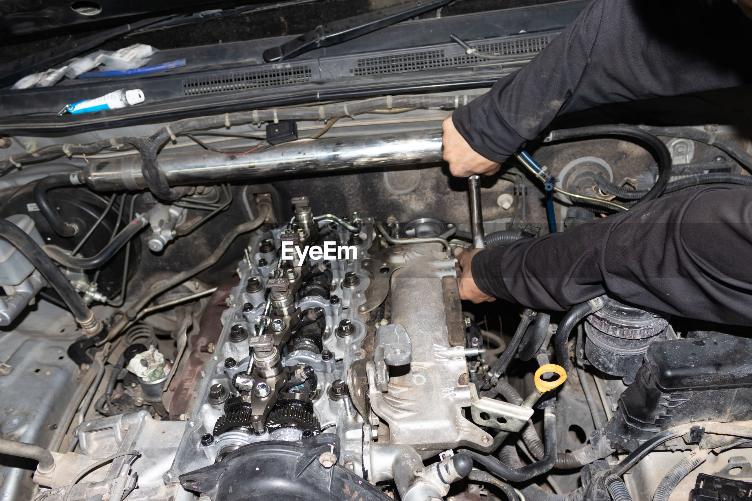 The mechanic is checking the engine.
