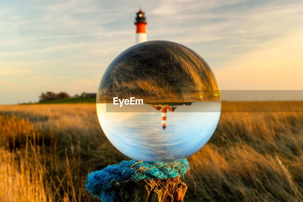 sky, land, sunset, nature, sphere, cloud - sky, field, plant, transparent, reflection, glass - material, crystal ball, landscape, scenics - nature, no people, grass, close-up, beauty in nature, outdoors, orange color