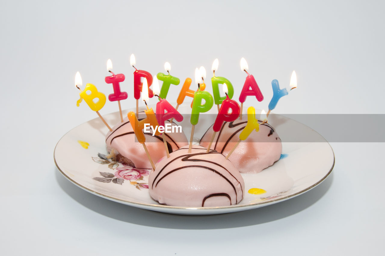 Close-up of lit birthday candles on cake over table