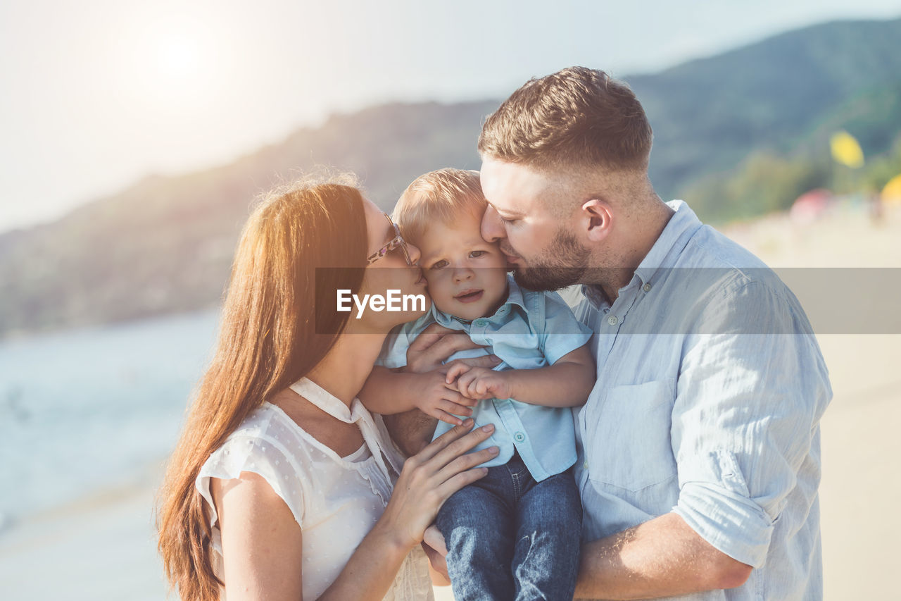 Couple kissing son while standing at beach against sky