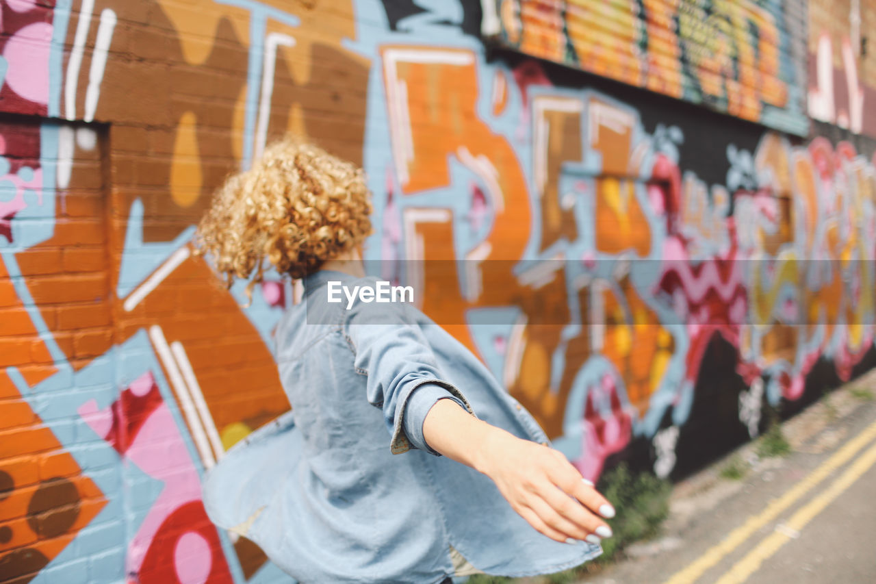 Side View Of Young Woman By Graffiti Wall
