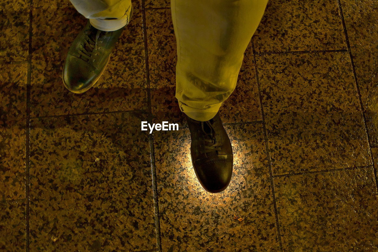 LOW SECTION OF MAN STANDING IN YELLOW SHOES