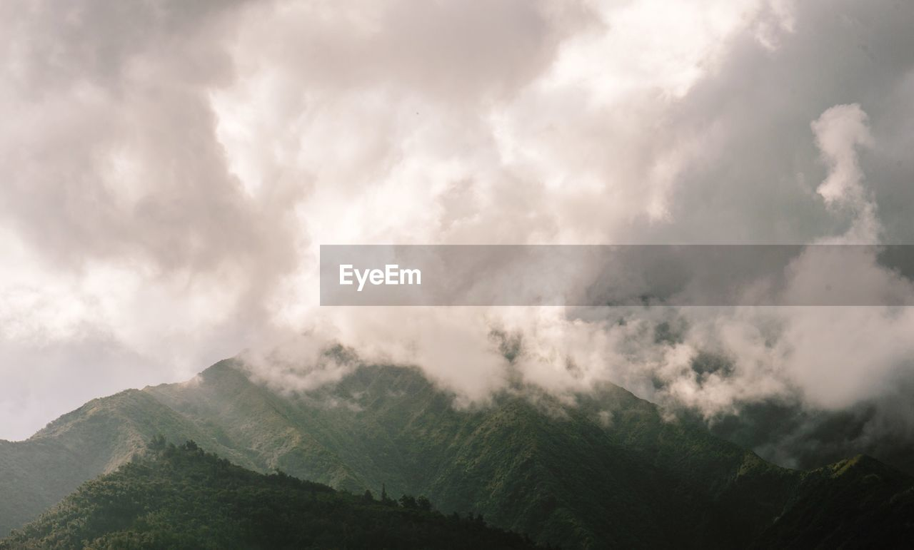 Scenic view of green mountains against cloudy sky
