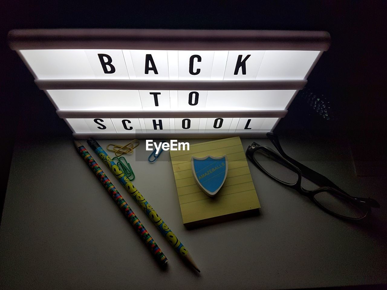 High angle view of illuminated sign with school supplies on table