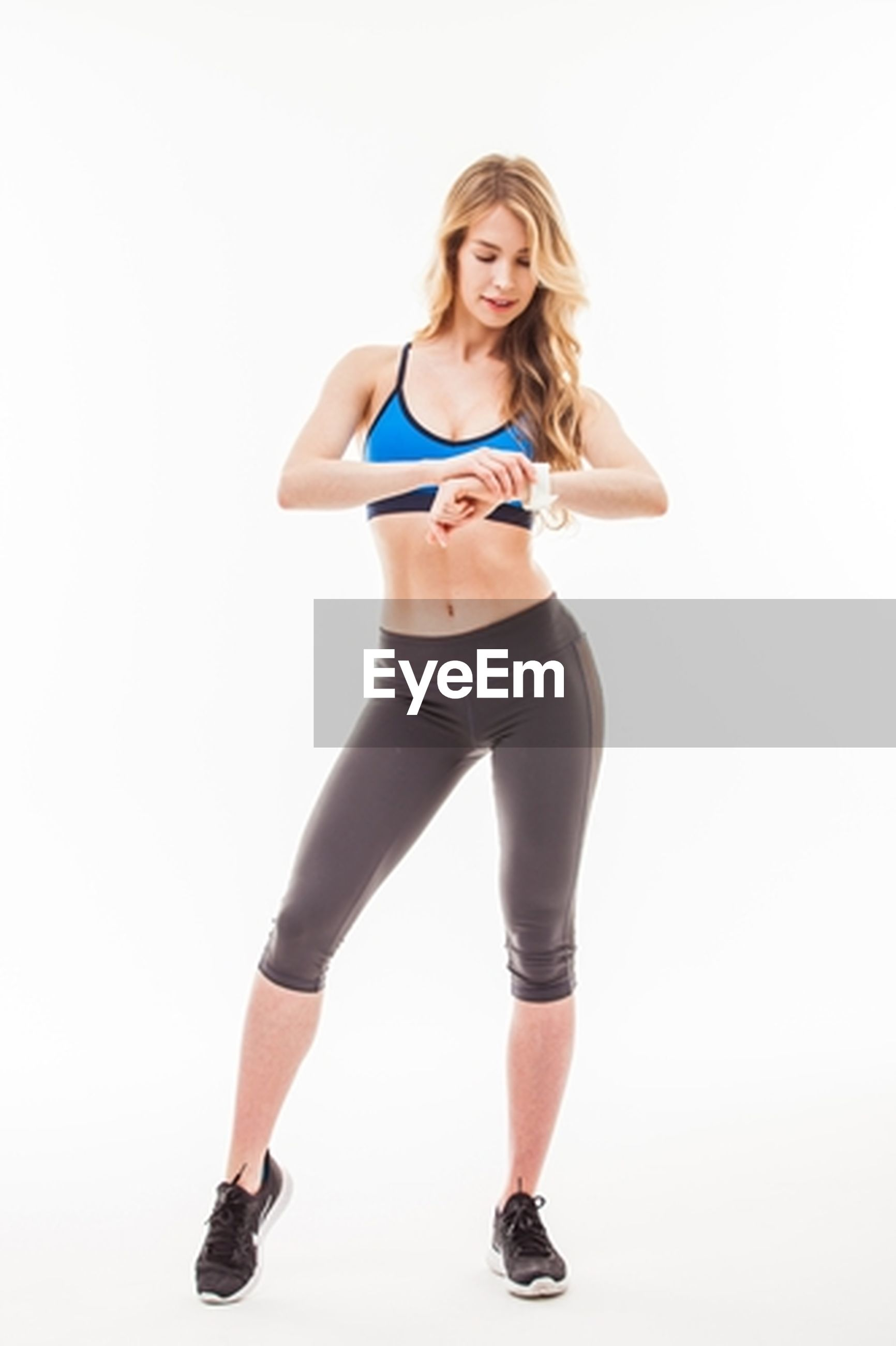 white background, full length, studio shot, young adult, exercising, sports clothing, one person, young women, healthy lifestyle, portrait, beautiful woman, sport, lifestyles, looking at camera, front view, one young woman only, wellbeing, standing, happiness, smiling, women, one woman only, only women, adult, adults only, day, people