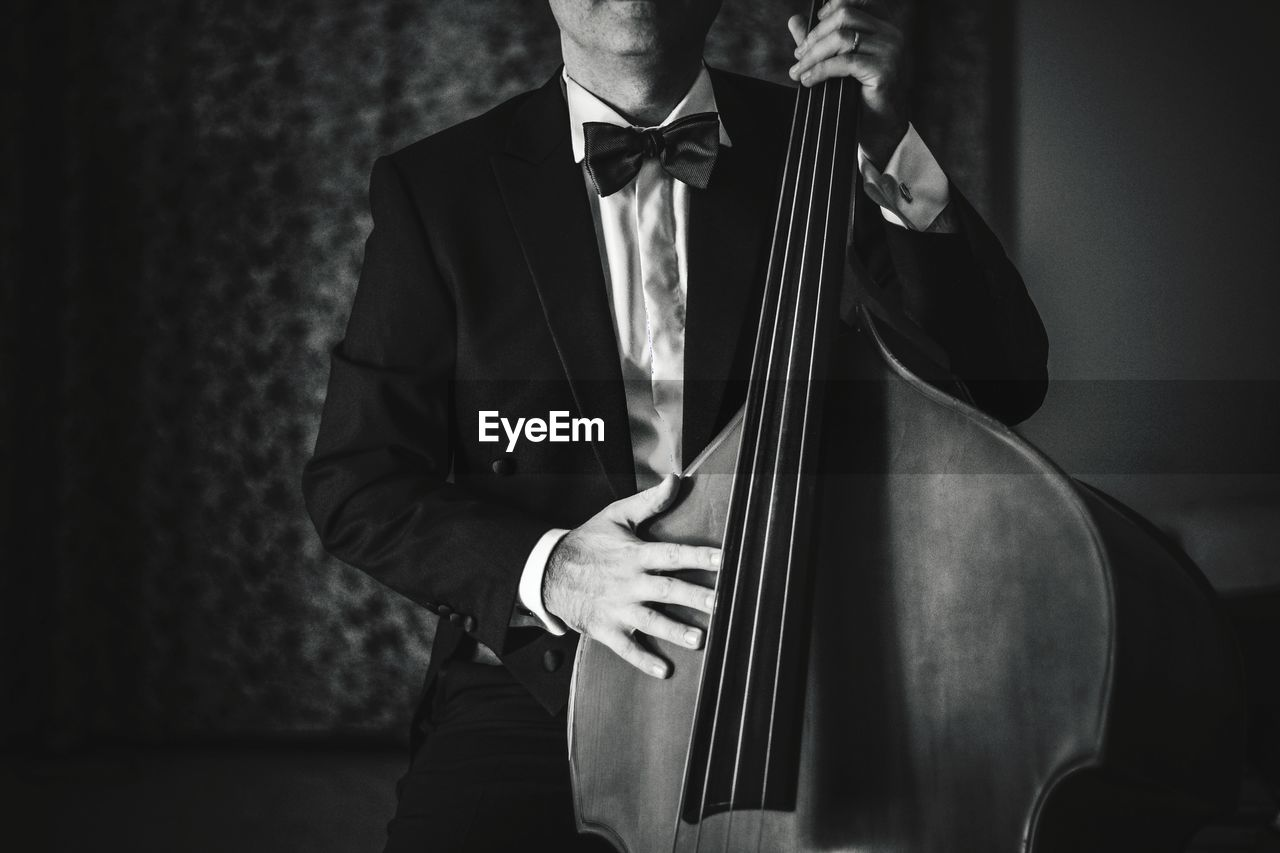 Full length of man playing double bass