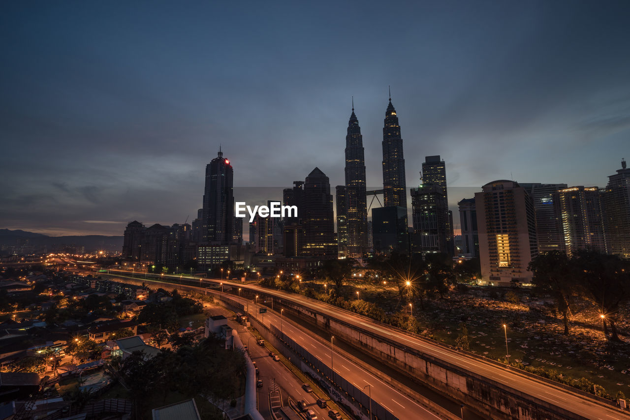 High Angle View Of Bridge By Petronas Towers Against Cloudy Sky At Night