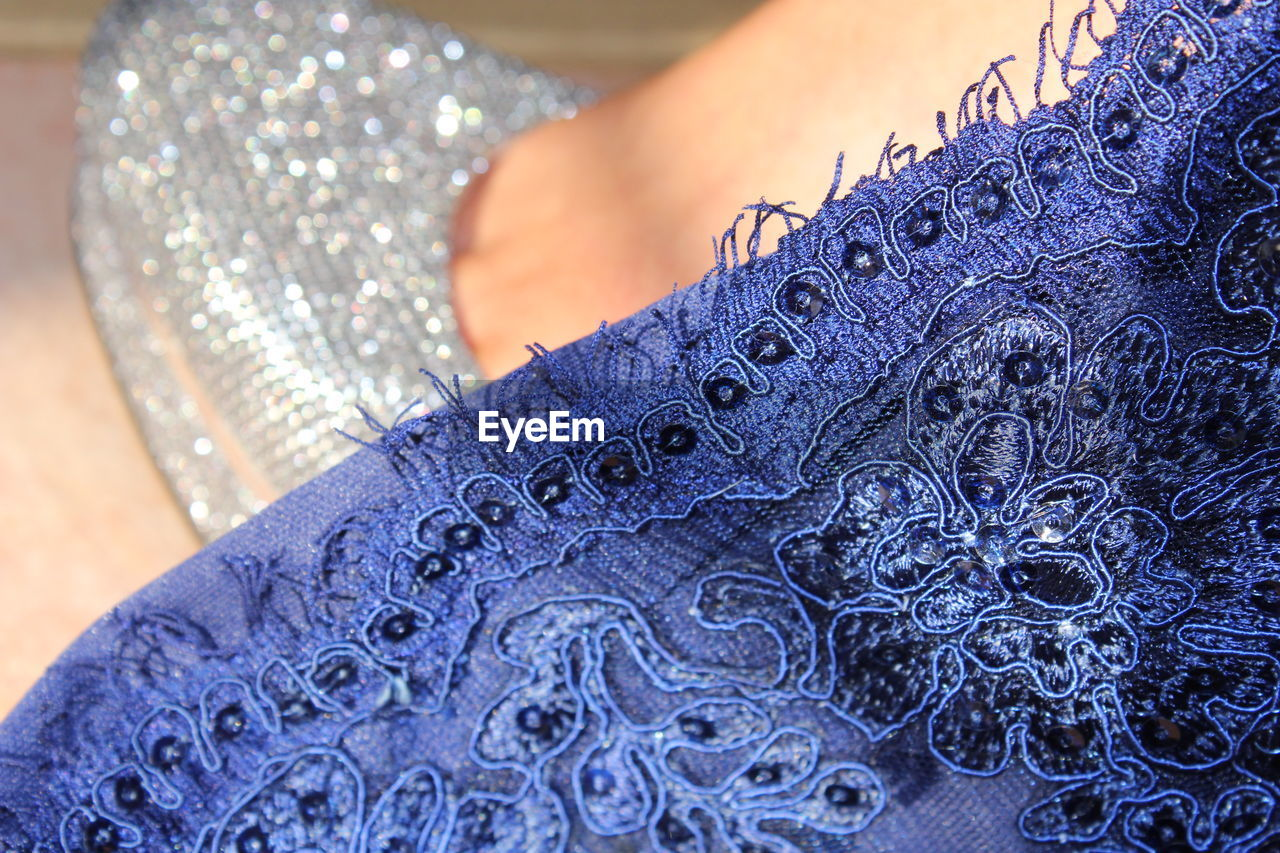 textile, close-up, pattern, blue, real people, one person, indoors, human body part, clothing, adult, selective focus, lifestyles, body part, women, focus on foreground, men, casual clothing, design, creativity, floral pattern, jeans, embroidery