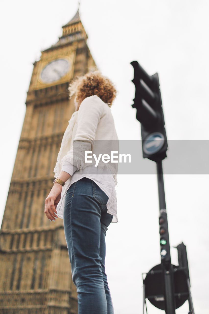 Low Angle View Of Woman Against Big Ben In City