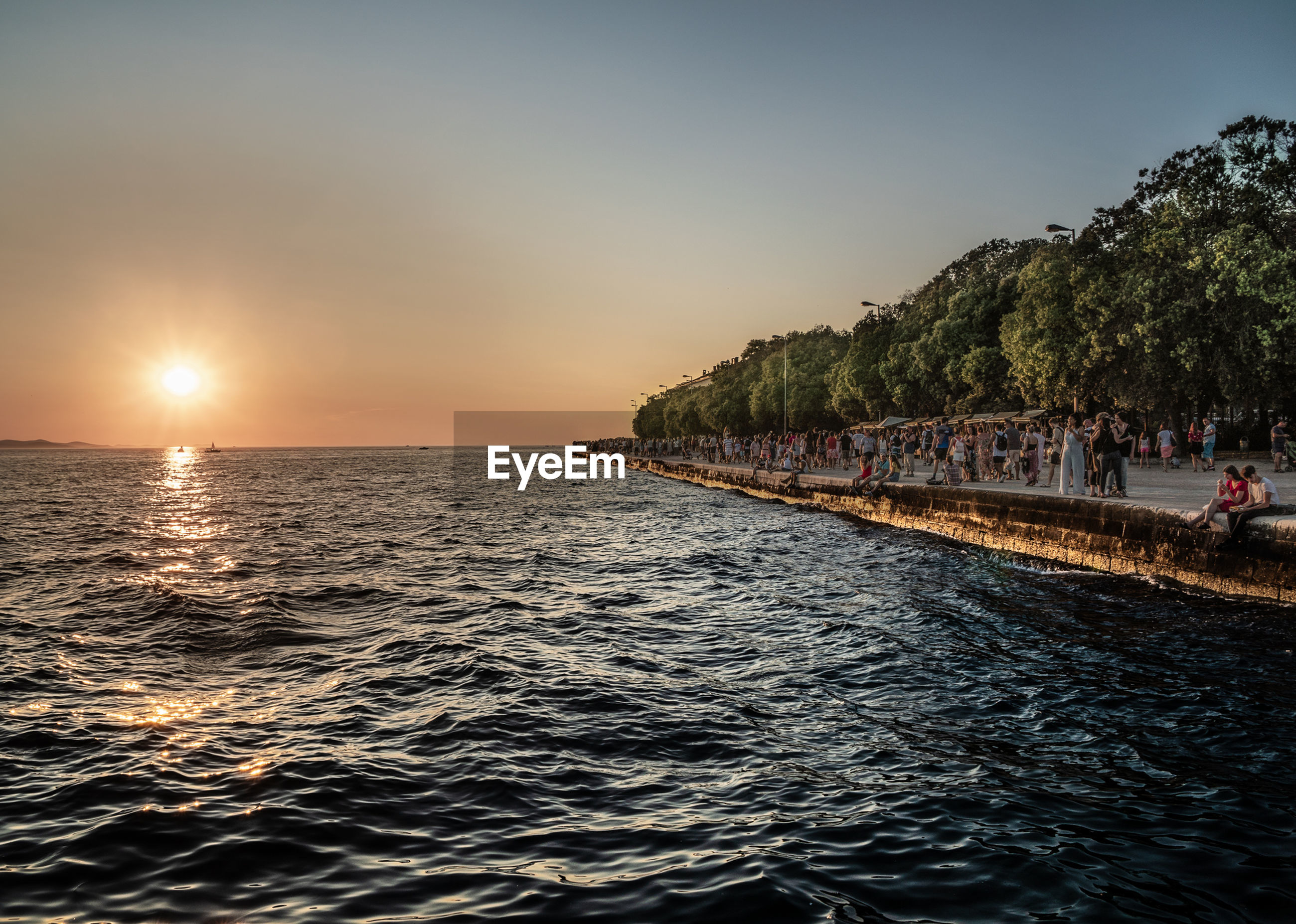 water, sky, sea, sunset, beauty in nature, scenics - nature, waterfront, tranquil scene, nature, tranquility, sun, idyllic, group of people, real people, land, rippled, clear sky, tree, large group of people, outdoors, horizon over water