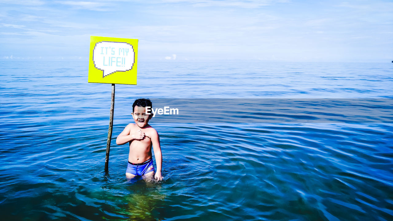 Little Shirtless Boy Standing By Sign In Sea
