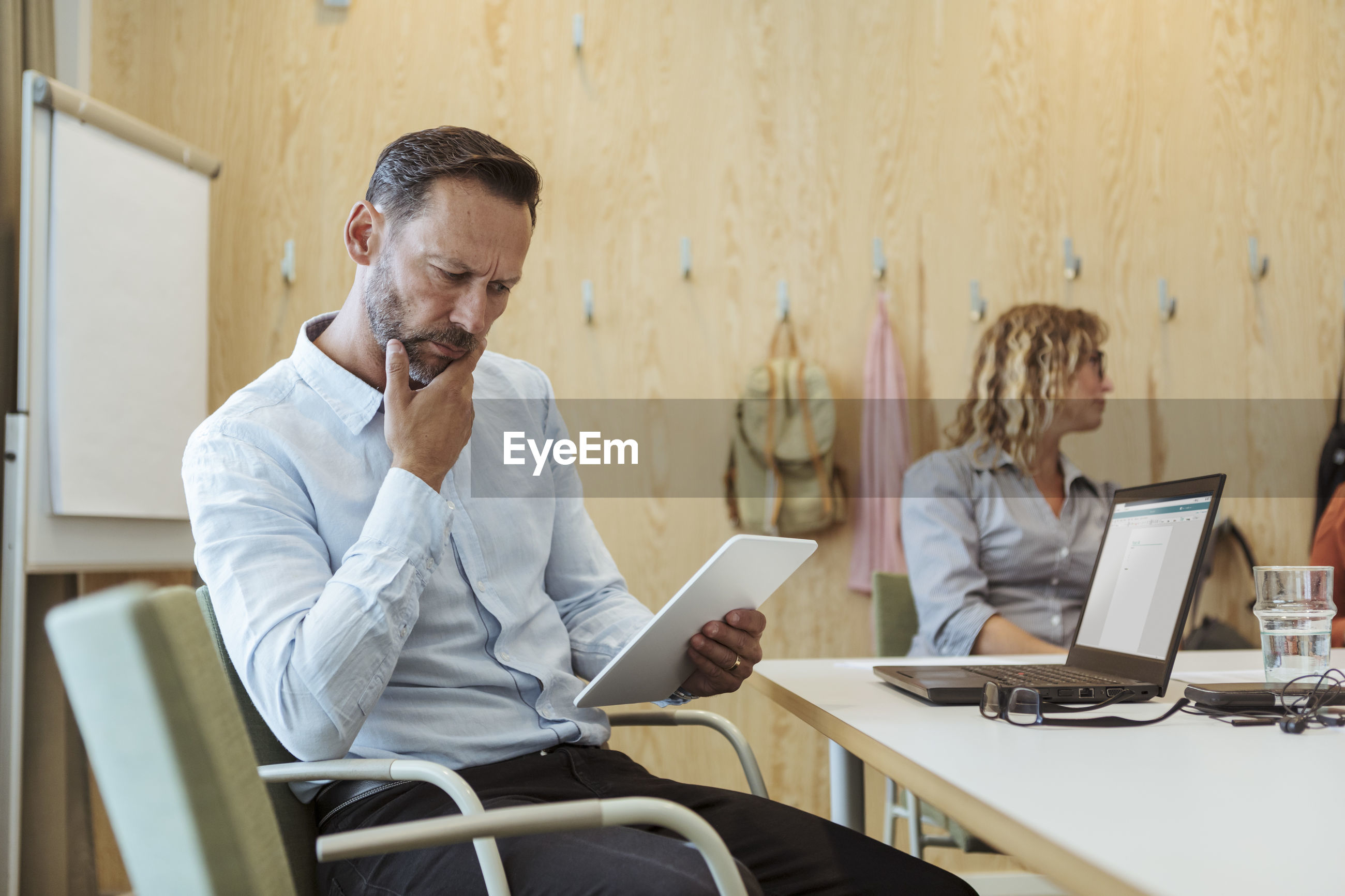 MAN USING MOBILE PHONE WHILE SITTING IN TABLE