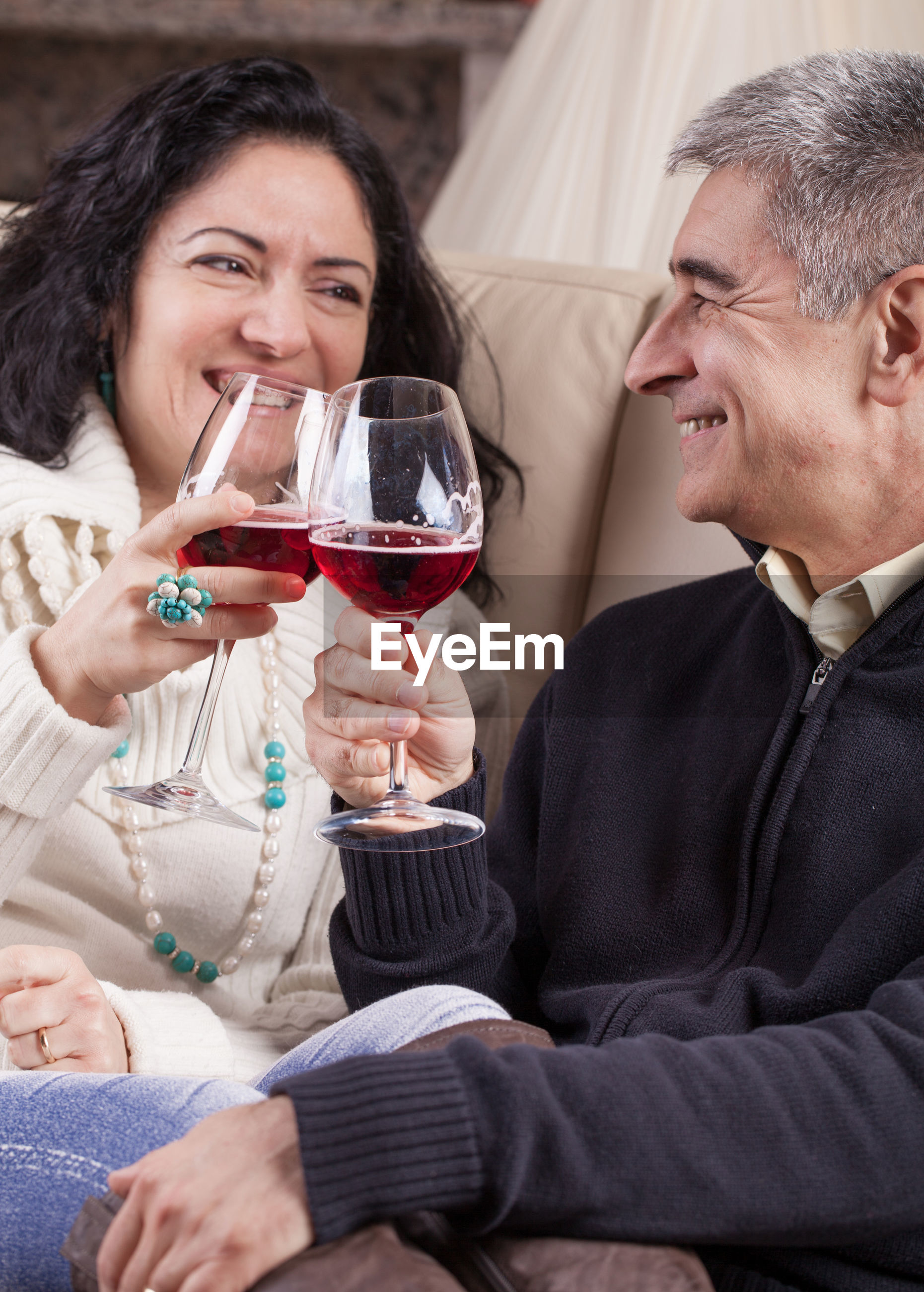 Happy mature couple toasting red wineglasses at home