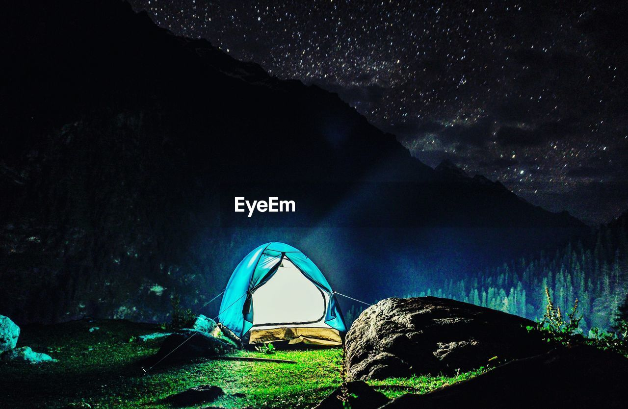night, beauty in nature, scenics - nature, mountain, nature, tranquil scene, sky, land, tent, camping, tranquility, adventure, tree, water, no people, forest, rock, illuminated, outdoors