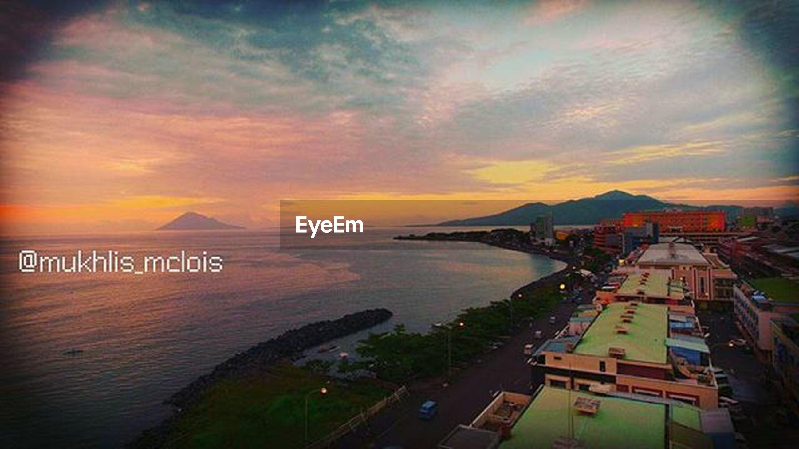 sunset, sea, sky, water, built structure, architecture, horizon over water, cloud - sky, orange color, scenics, building exterior, beach, beauty in nature, tranquil scene, nature, tranquility, shore, cloudy, cloud, idyllic