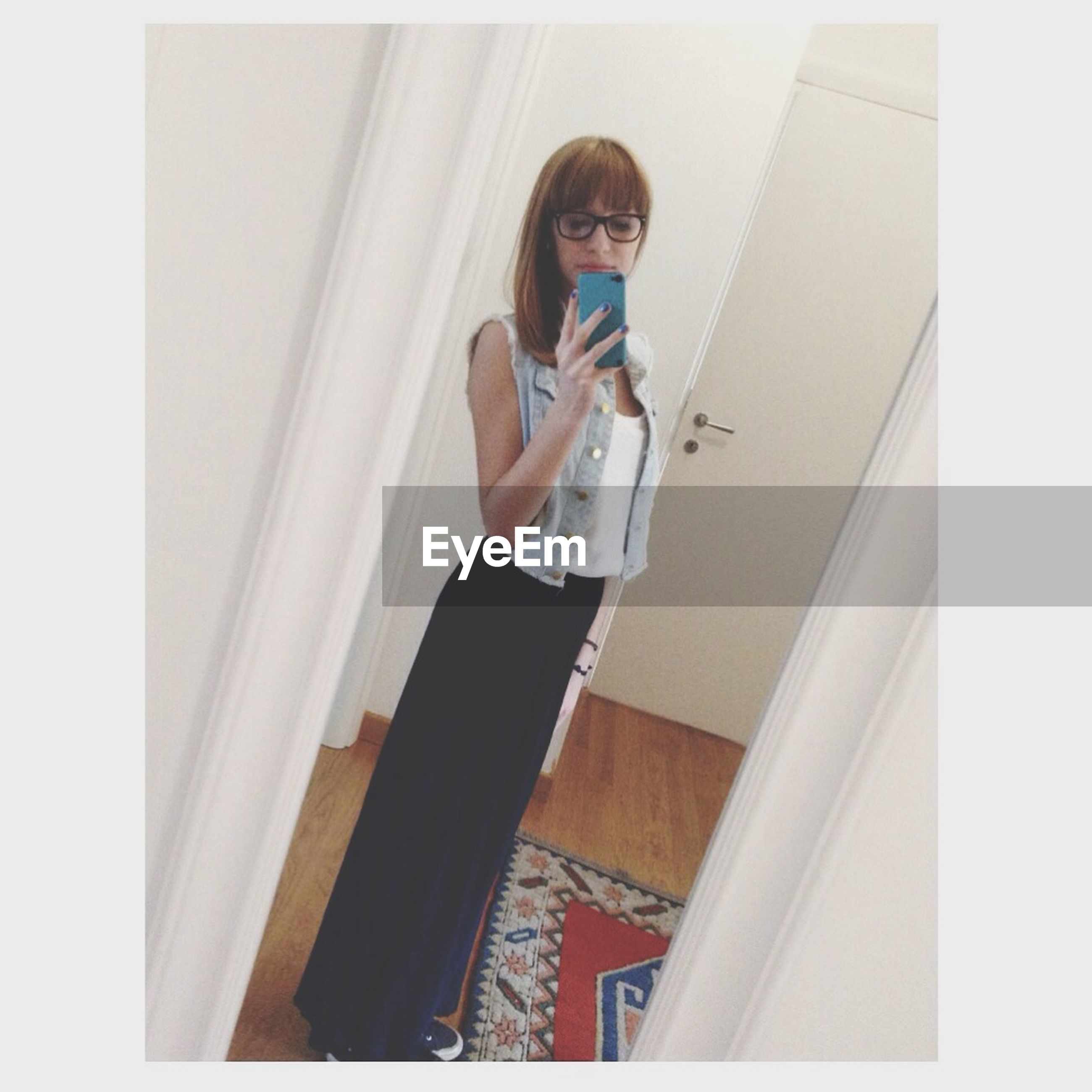 indoors, young adult, lifestyles, person, young women, casual clothing, leisure activity, full length, standing, front view, auto post production filter, three quarter length, home interior, transfer print, wall - building feature, wireless technology, looking at camera