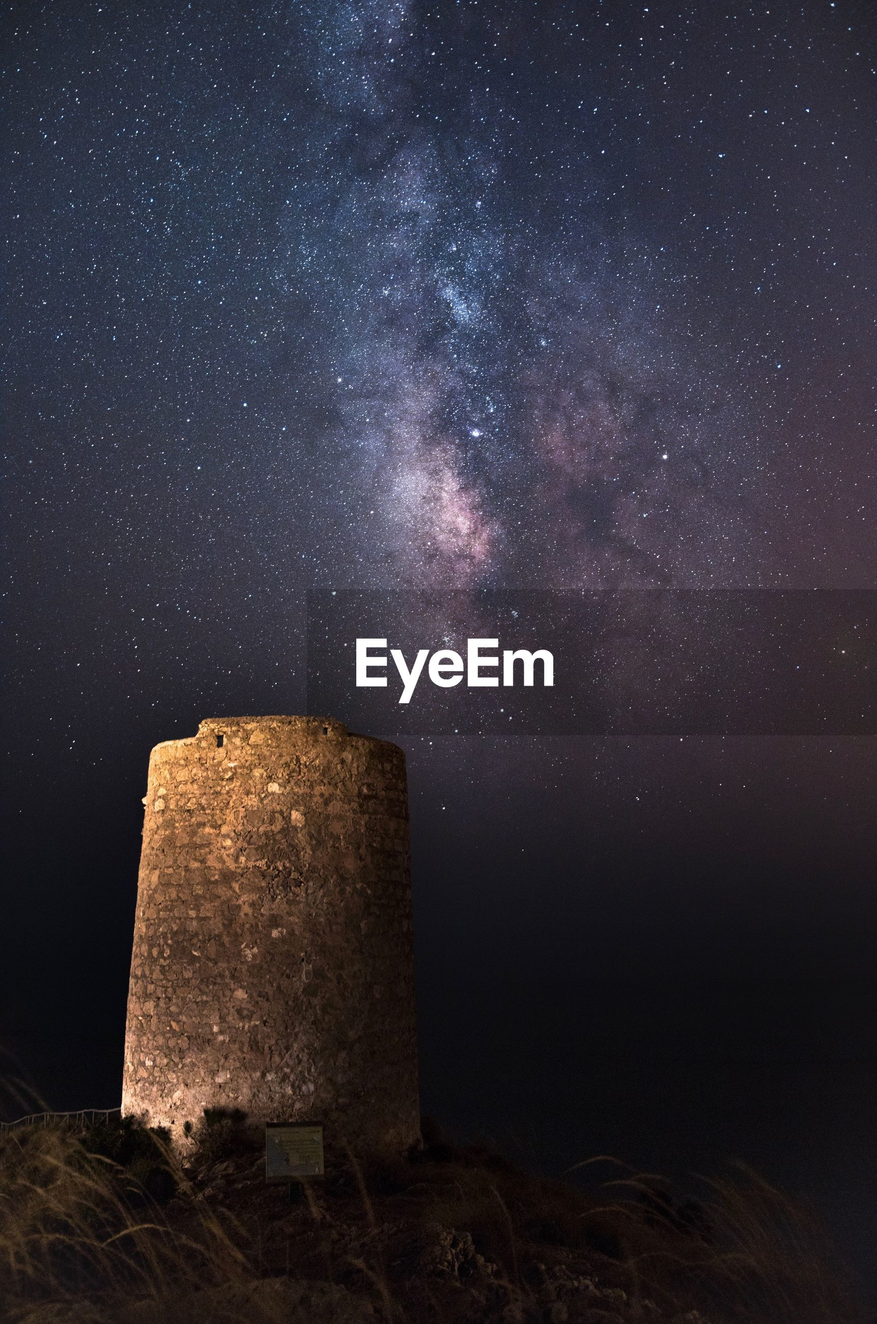 Scenic view of built structure against star field at night