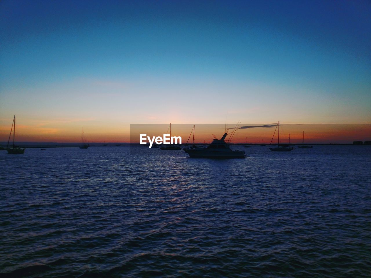 sunset, water, sea, nautical vessel, transportation, mode of transport, boat, nature, waterfront, scenics, outdoors, beauty in nature, tranquility, no people, tranquil scene, silhouette, rippled, sky, blue, mast, sailing, sailboat, horizon over water, clear sky, harbor, day
