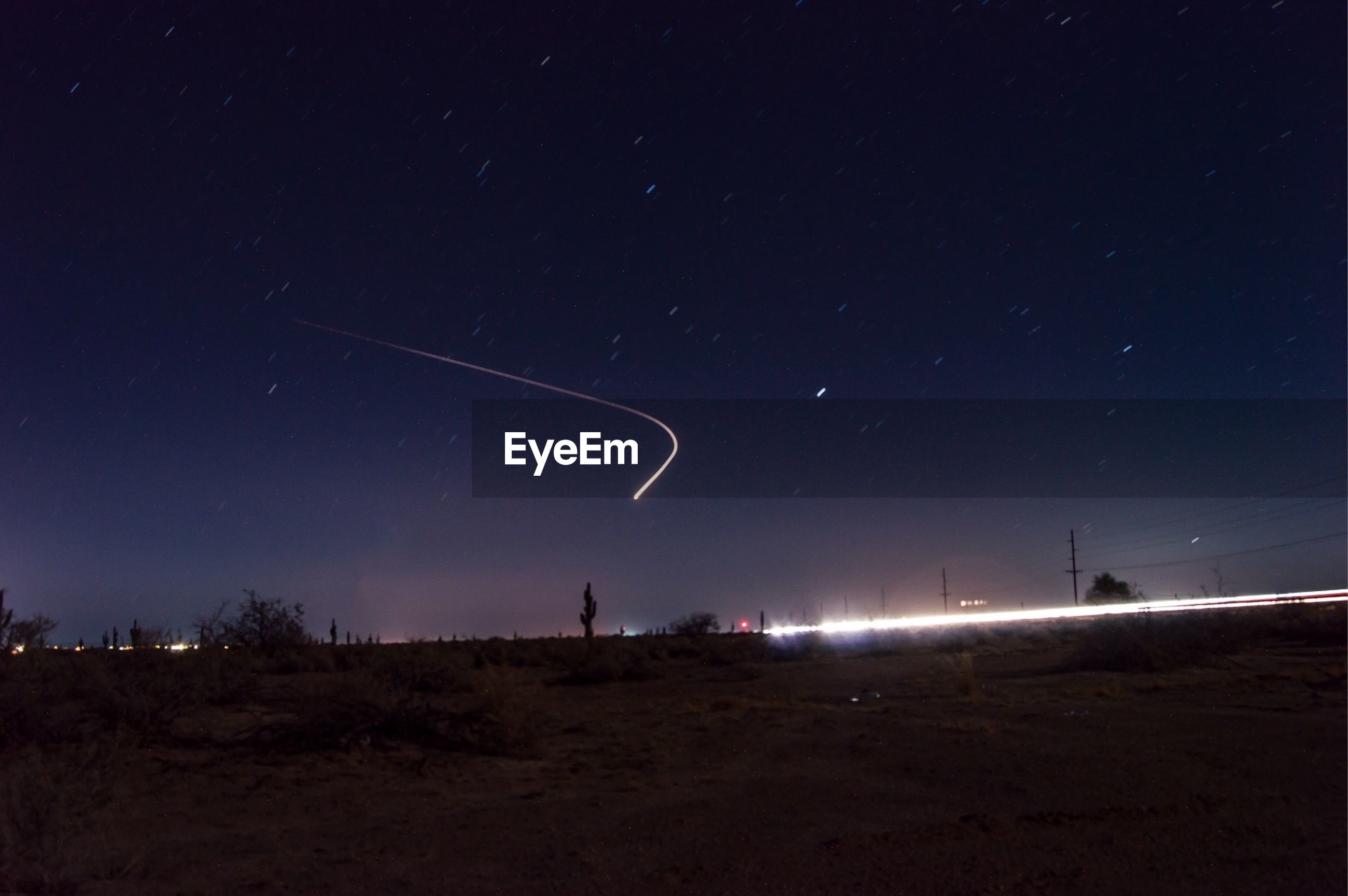 Scenic view of star trail in sky over landscape at night
