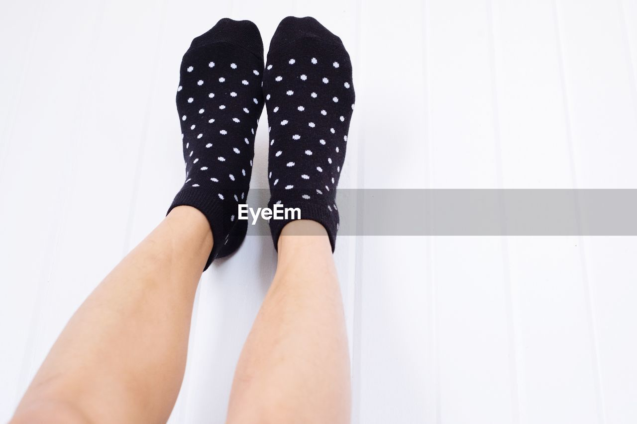 Low section of woman wearing socks against white background