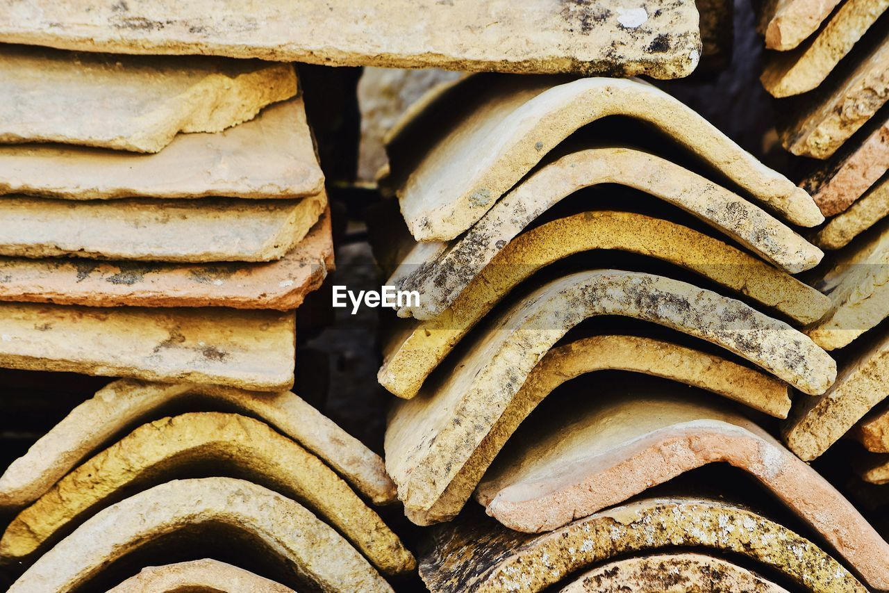 full frame, backgrounds, no people, close-up, stack, day, pattern, old, large group of objects, roof tile, wood - material, metal, textured, outdoors, still life, focus on foreground, damaged, wheel, rusty, abundance, deterioration