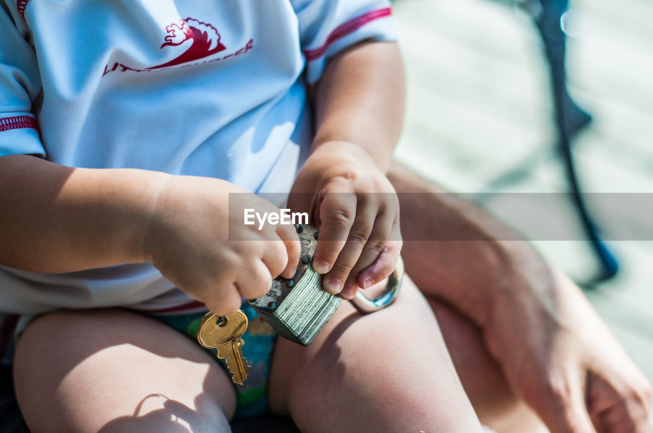 Midsection Of Kid Playing With Padlock And Key