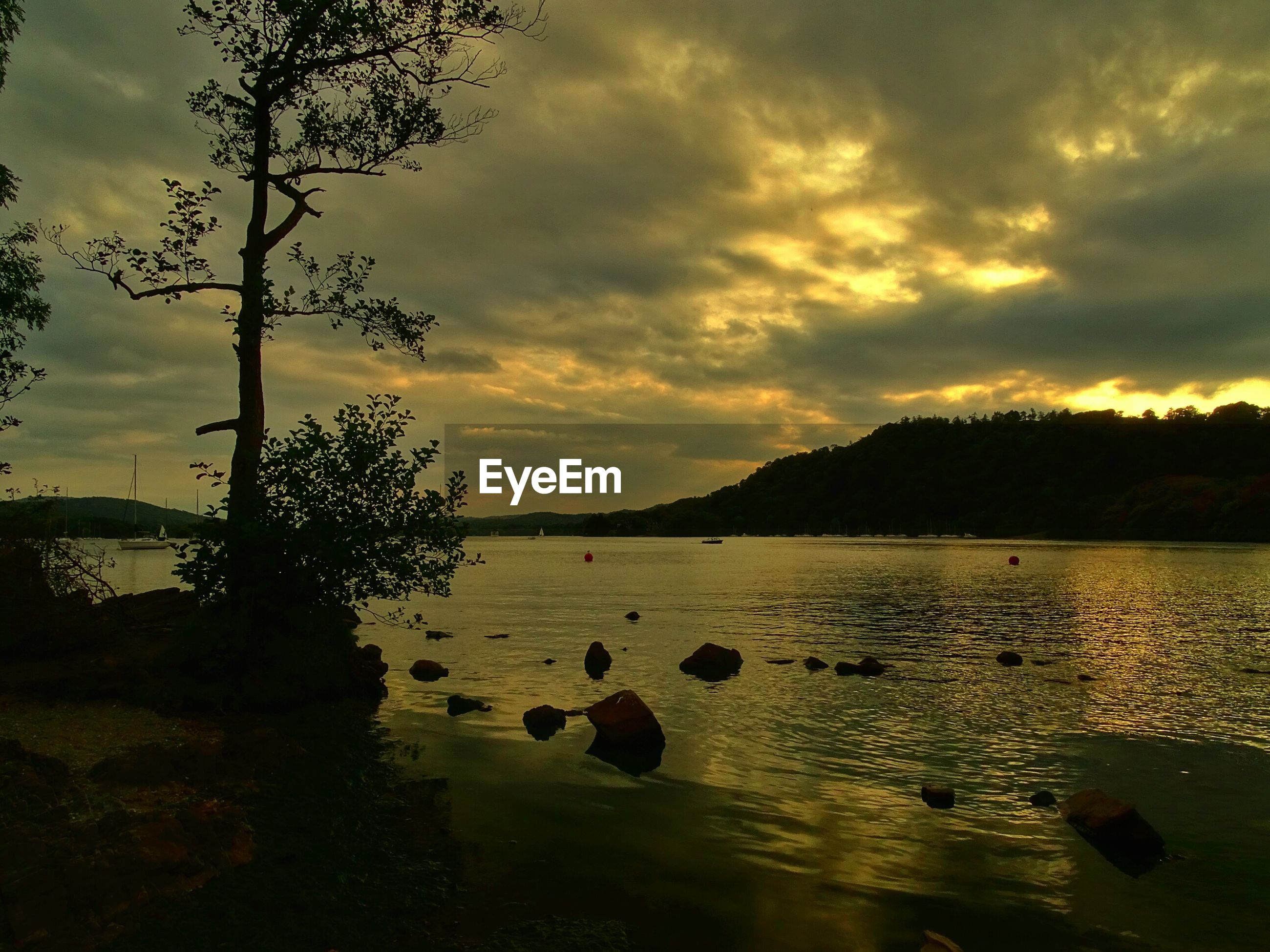 Scenic view of lake against cloudy sky at sunset