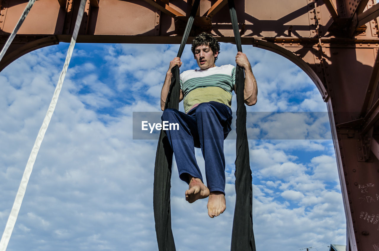 low angle view, sky, cloud - sky, day, real people, one person, childhood, boys, leisure activity, outdoors, built structure, hanging, lifestyles, people