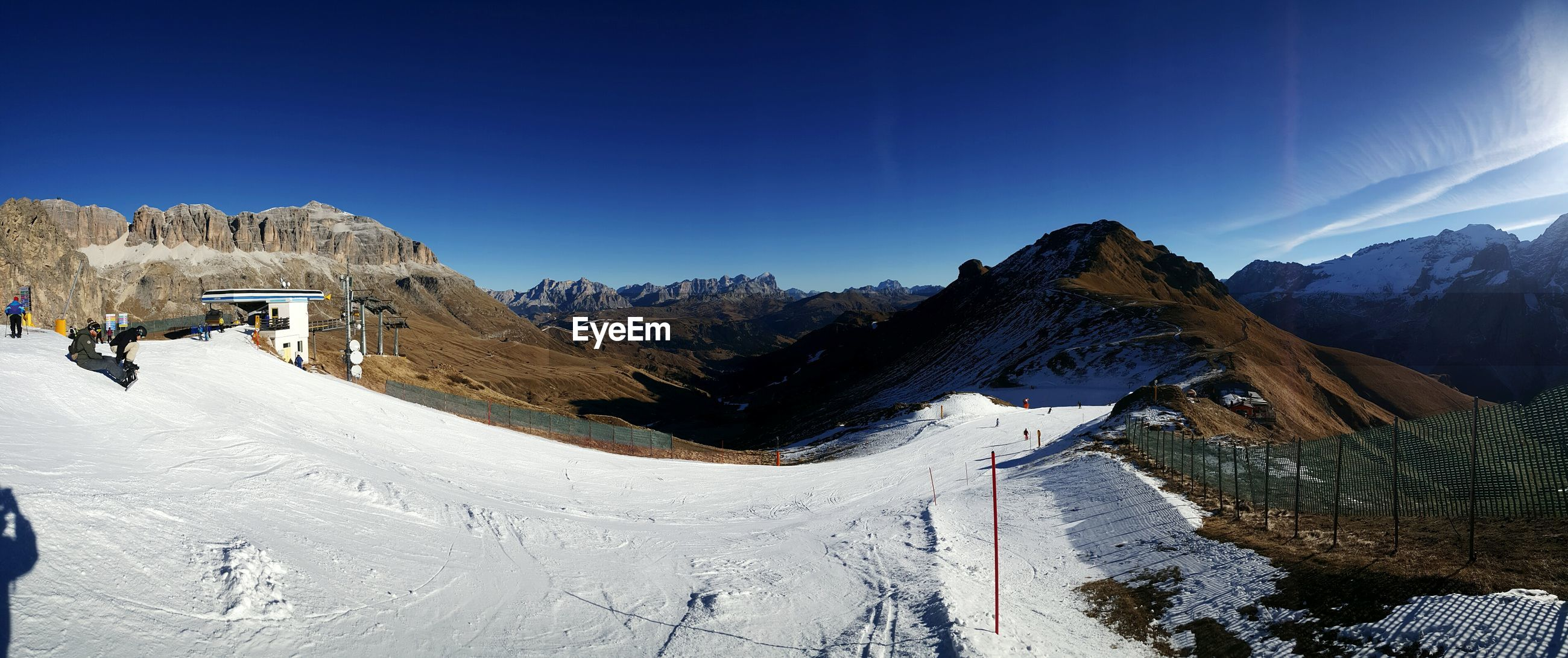 Panoramic shot of snow covered mountains against clear blue sky