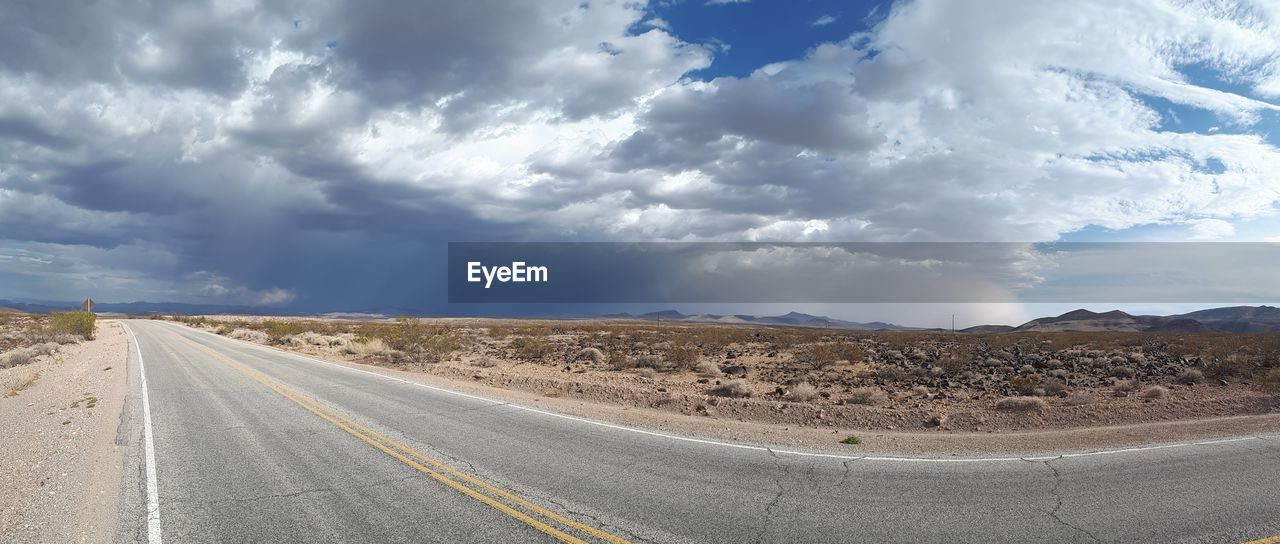 cloud - sky, road, sky, transportation, direction, landscape, sign, the way forward, road marking, symbol, environment, marking, day, desert, no people, nature, scenics - nature, diminishing perspective, empty road, non-urban scene, outdoors, arid climate, climate