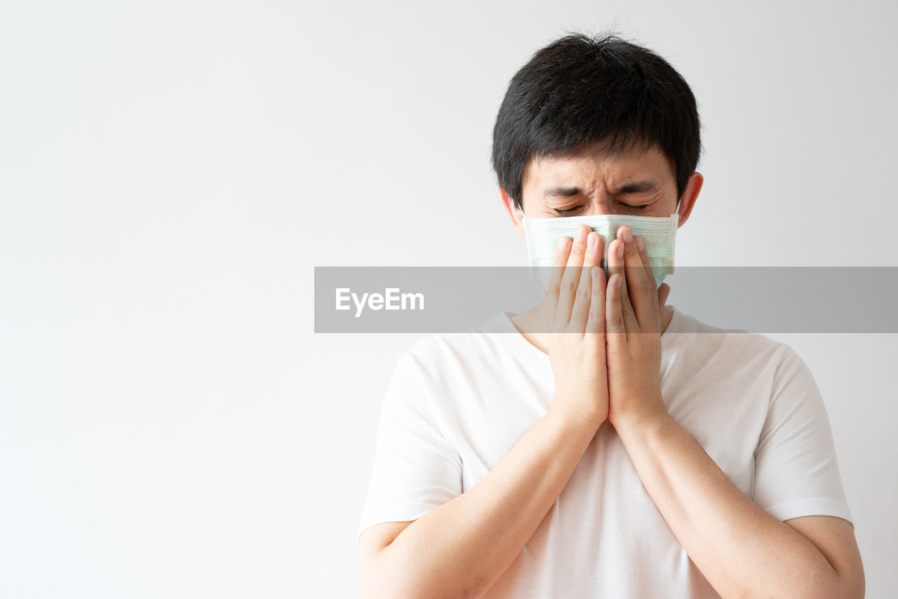 PORTRAIT OF MAN COVERING FACE WITH WHITE BACKGROUND