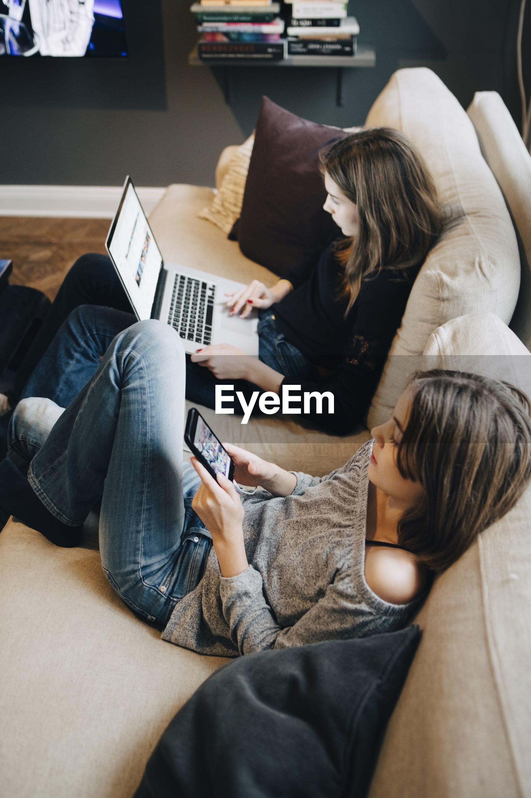 Smiling girls using laptop and mobile phone while resting on sofa at home