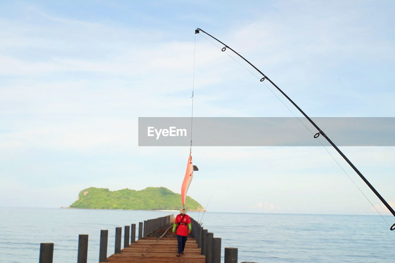 water, sky, one person, cloud - sky, real people, sea, nature, fishing, lifestyles, leisure activity, rod, day, fishing rod, beauty in nature, holding, scenics - nature, standing, outdoors, horizon over water, human arm, arms raised
