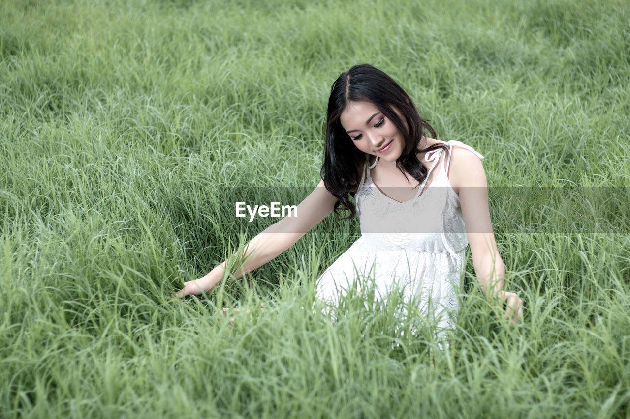 grass, plant, young adult, one person, smiling, leisure activity, field, land, women, green color, three quarter length, looking at camera, beautiful woman, beauty, portrait, nature, young women, lifestyles, day, hair, hairstyle, outdoors