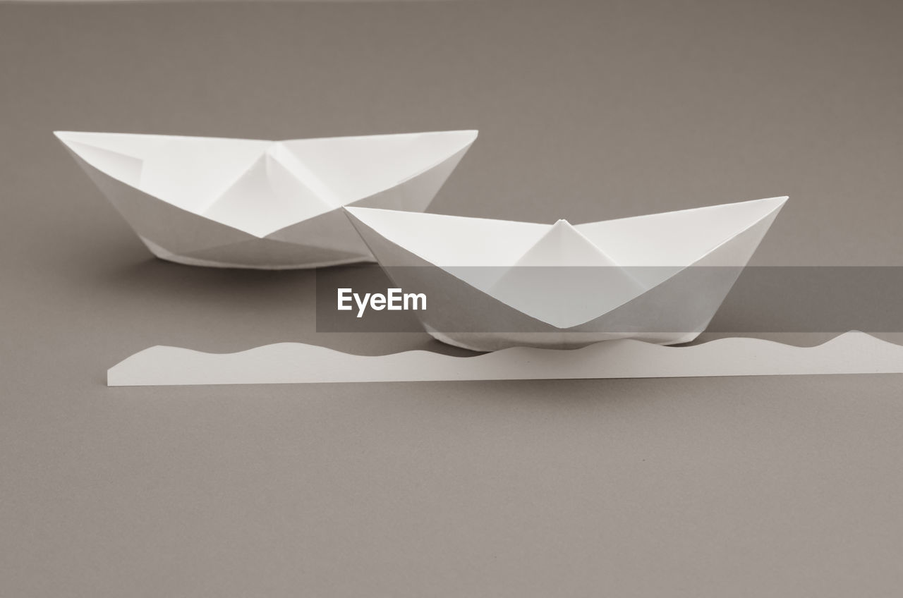 paper boat, paper, art and craft, creativity, craft, studio shot, no people, indoors, still life, origami, close-up, white color, folded, copy space, table, high angle view, gray background, shape, white background, single object