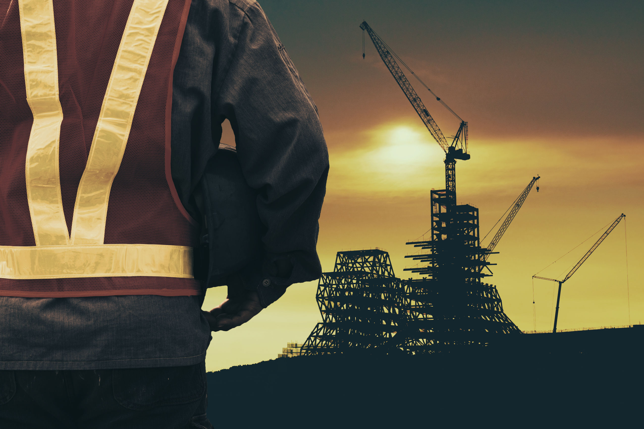 Midsection of construction worker holding hardhat while standing against incomplete building during sunset
