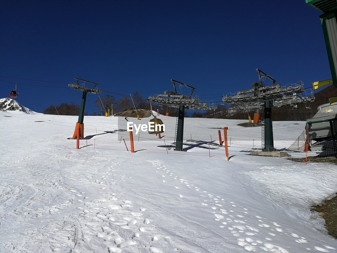 winter, cold temperature, snow, sky, nature, clear sky, day, sport, land, blue, sunlight, white color, frozen, field, covering, beauty in nature, built structure, architecture, copy space, outdoors, no people, snowcapped mountain, ski resort